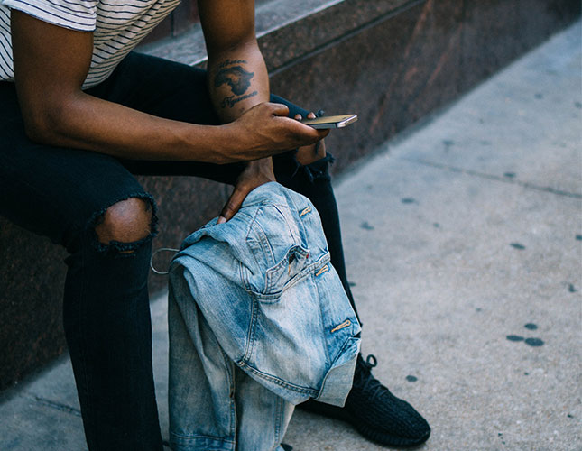 Man holding jacket sitting on step on mobile phone outside