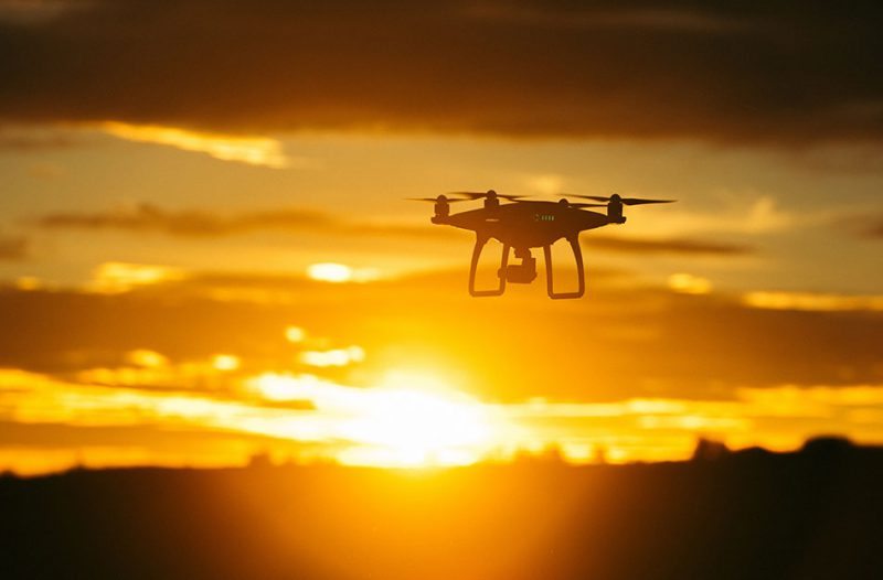Drone flying in front of sunset
