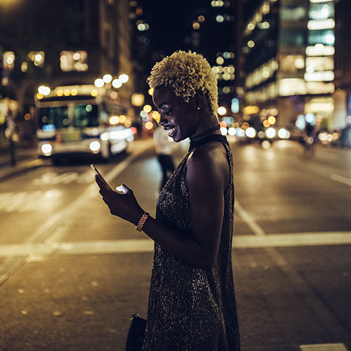 lady looking at phone against city at night backdrop