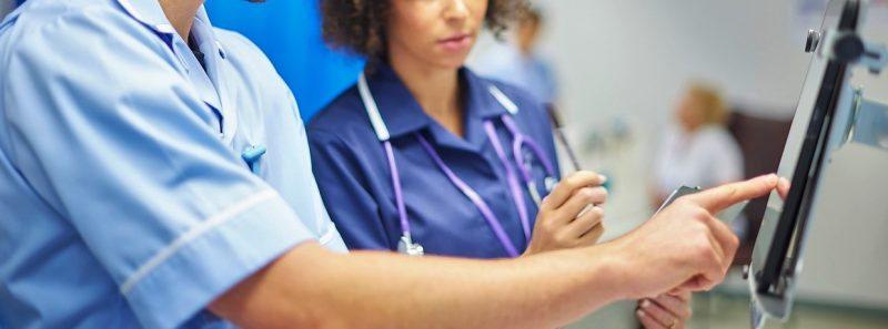 a male nurse checks the dosage on his digital tablet supervised by his staff nurse