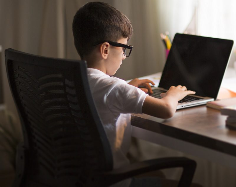 young boy doing homework on laptop