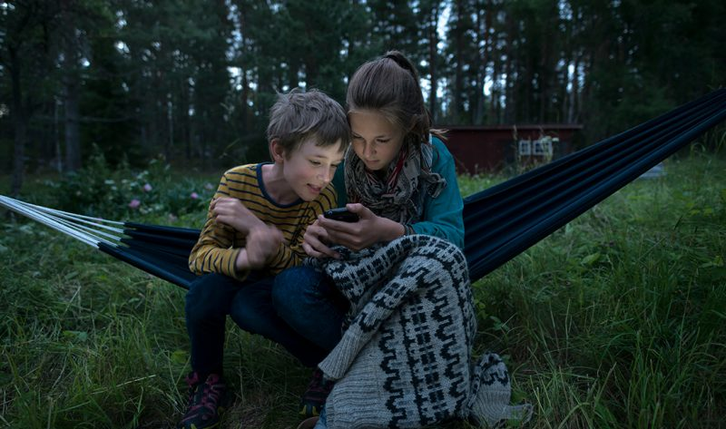 Two young people sat outside on mobile phone