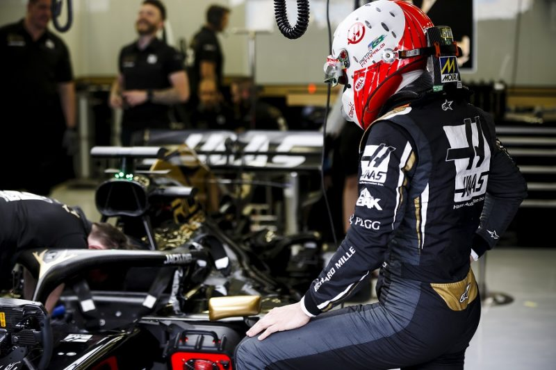 Haas driver looking at his car