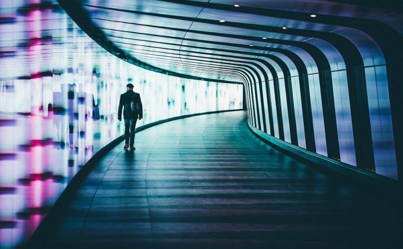 man walking through tunnel