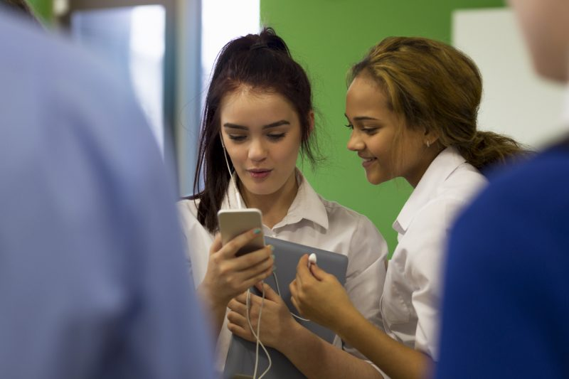Female Students Watching Videos on Smartphone