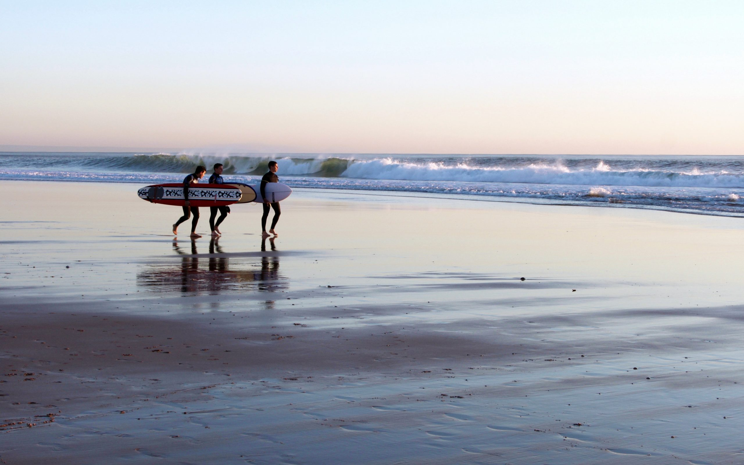 three men carrying surfboards on a beach at dusk