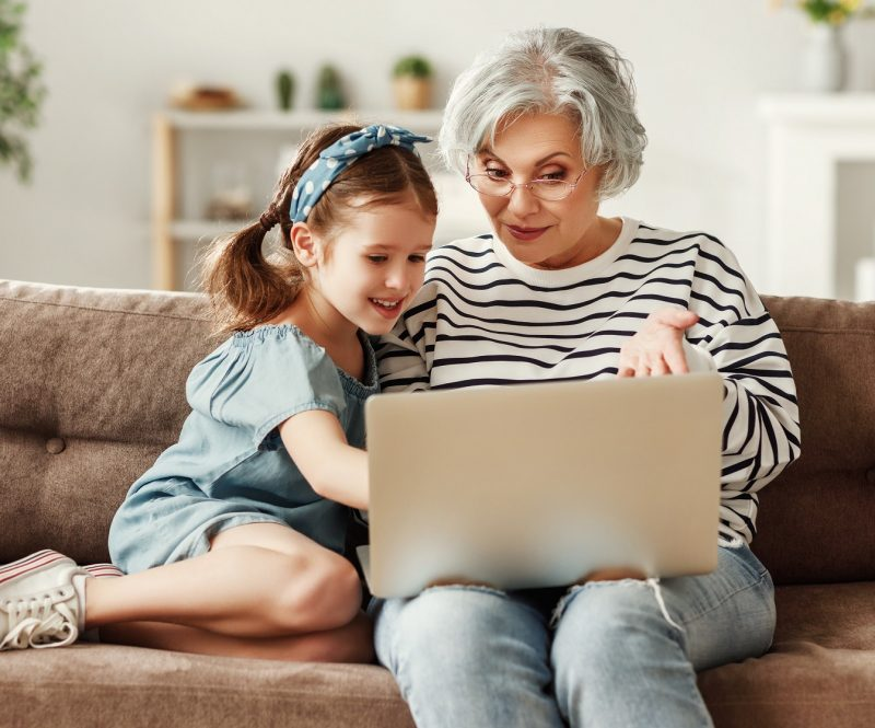 Little child girl with grandmother using laptop at home